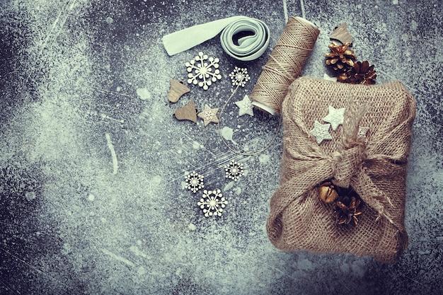 Kerstcadeau verpakt in jute. linnen koord en houten versieringen