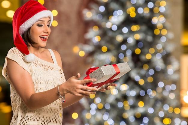 Kerstcadeau. verraste vrouw over bokeh kerstverlichting