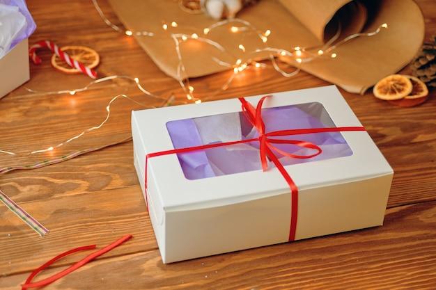 Kerstcadeaudoos met transparant deksel op houten tafelverpakking ambachtelijke papieren slinger lolly's en ...