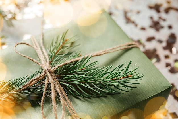 Kerstcadeaudoos verpakt in groen kraftpapier en versierd met dennenboomtak en kerstverlichting glitters
