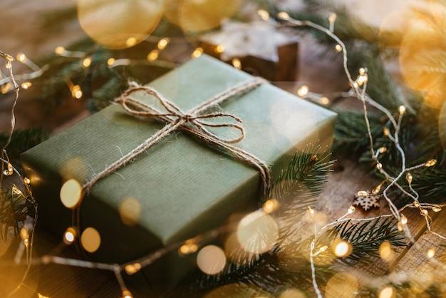 Kerstcadeaudoos verpakt in groen kraftpapier en versierd met dennenboomtak en kerstverlichting schittert op feestelijke nieuwjaarsachtergrond