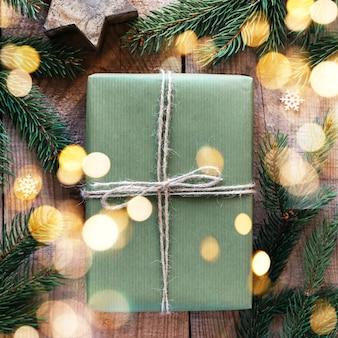 Kerstcadeaudoos verpakt in groen kraftpapier en versierd met dennenboomtak op feestelijke nieuwjaarsachtergrond