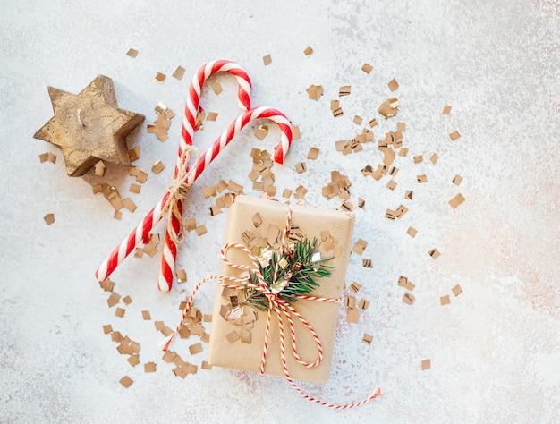 Kerstcadeaudoos verpakt in kraftpapier, zuurstokken en kerststerkaars greeing card