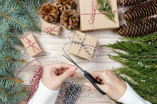 Kerstcadeaupapier. vrouwelijke handen die kerstmisheden verpakken dat in kraftpapier-document hoogste mening wordt verpakt. wintervakantie plat leggen vrouw met kerstcadeau doos
