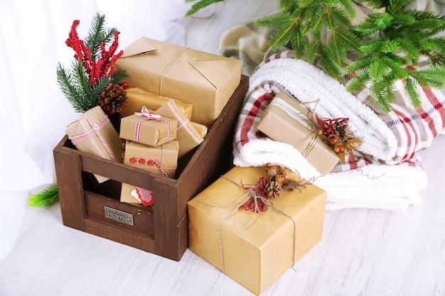 Kerstcadeaus en decoraties in dozen bij de kerstboom op lichte achtergrond on