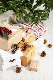 Kerstcadeaus en decoraties in dozen bij de kerstboom op lichte ondergrond