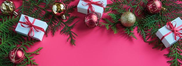 Kerstcadeaus en feestelijk decor op een roze achtergrond. bannerformaat.