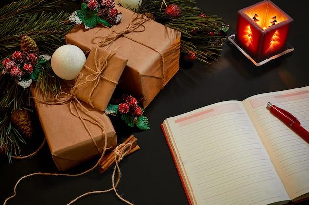 Kerstcadeaus en notebook liggen in de buurt van groene sparren tak op zwarte achtergrond bovenaanzicht. ruimte kopiëren. stilleven. plat leggen. nieuwjaar