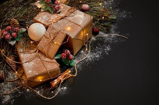 Kerstcadeaus en slinger in de buurt van groene sparren tak op een zwarte achtergrond. kerstmis achtergrond. bovenaanzicht. ruimte kopiëren. stilleven. plat leggen. nieuwjaar