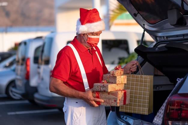 Kerstcadeaus in de handen van een oudere man met kerstmuts en bretels die een chirurgisch masker dragen