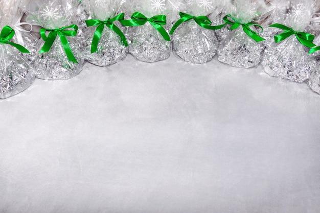 Kerstcadeaus in de vorm van foliezakken en doorzichtige film vastgebonden met een strik van een groen lint met daarop sneeuwvlokken op een grijze achtergrond.