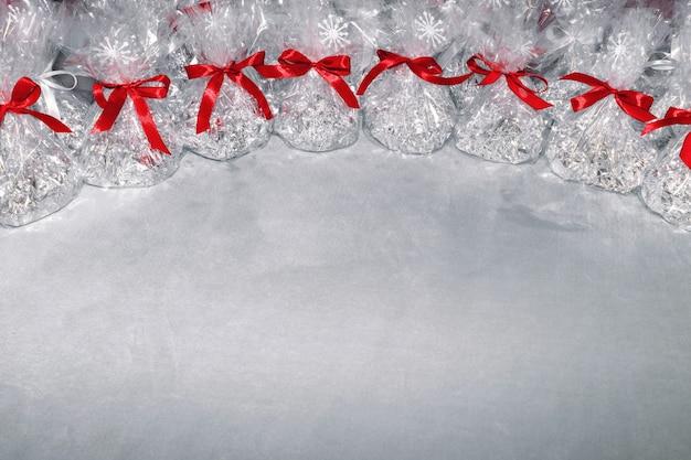 Kerstcadeaus in de vorm van foliezakken en transparante film vastgebonden met een strik van een rood lint met daarop sneeuwvlokken op een grijze achtergrond.