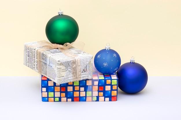 Kerstcadeaus in dozen en kerstballen op een gekleurde achtergrond
