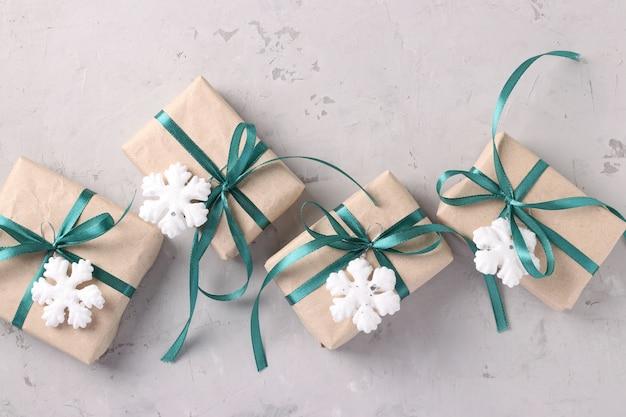 Kerstcadeaus in kraftpapier met groene linten op grijs