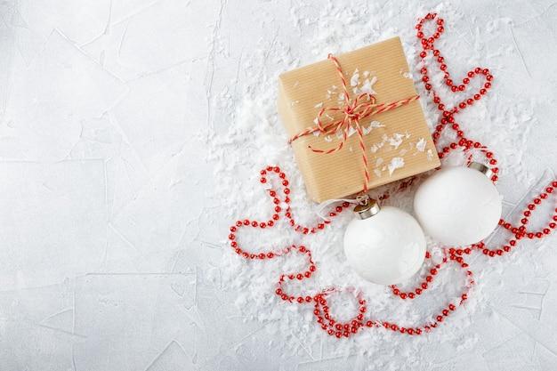 Kerstcadeaus in kraftpapier, rode kralen, witte kerstballen en dennentakken op een met sneeuw bedekte ondergrond. bovenaanzicht