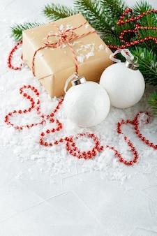 Kerstcadeaus in kraftpapier, rode kralen, witte kerstballen en dennentakken op een met sneeuw bedekte tafel