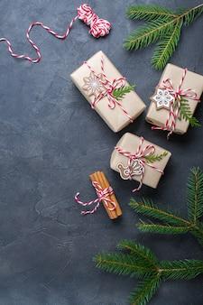 Kerstcadeaus inpakken. geschenkdozen en decoraties, pijnboomtakken op donkere tafel.