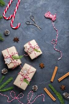 Kerstcadeaus inpakken. kerst geschenkdozen en decoraties, pijnboomtakken op donkere tafel. plat leggen
