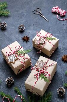 Kerstcadeaus inpakken. kerst geschenkdozen en decoraties, pijnboomtakken op donkere tafel.