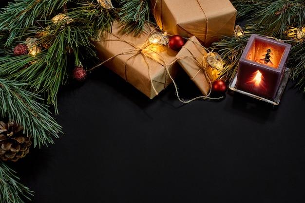 Kerstcadeaus, kerstboom, kaarsen, gekleurd decor, sterren, ballen op zwarte achtergrond. bovenaanzicht. ruimte kopiëren. stilleven plat liggend nieuwjaar