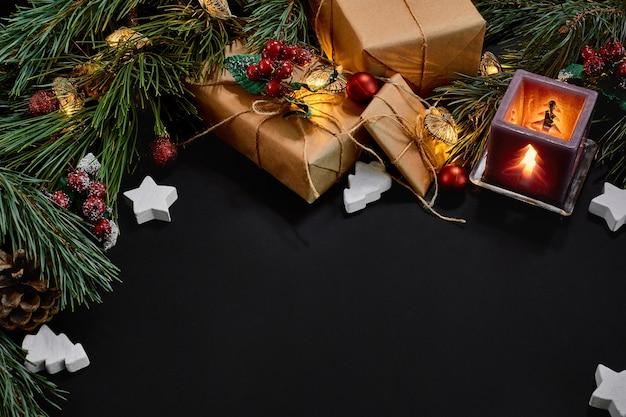 Kerstcadeaus, kerstboom, kaarsen, gekleurd decor, sterren, ballen op zwarte achtergrond. bovenaanzicht. ruimte kopiëren. stilleven plat liggend nieuwjaar Premium Foto