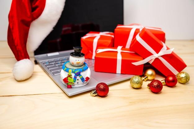 Kerstcadeaus kopen met laptop. gelukkig nieuwjaar. wintervakantie verkoop. bonus voor online aankopen. digitale tablet in de kersttijd. feestelijk surfen en winkelen met een creditcard tijdens de kerstperiode.