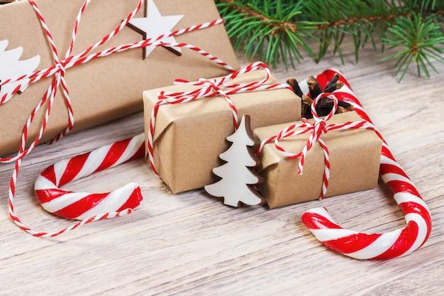 Kerstcadeaus met dennenboom en decoratieve kegel, snoep en geschenken voor vakantie, gekleurd snoep, sneeuwvlokken, kerstmis en gelukkig nieuwjaar samenstelling, plat lag, bovenaanzicht