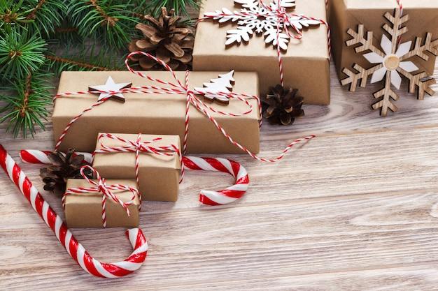 Kerstcadeaus met dennenboom en decoratieve kegel. snoepjes en geschenken voor vakanties. gekleurd snoep. sneeuwvlokken. kerstmis en gelukkig nieuwjaar samenstelling. plat lag, bovenaanzicht