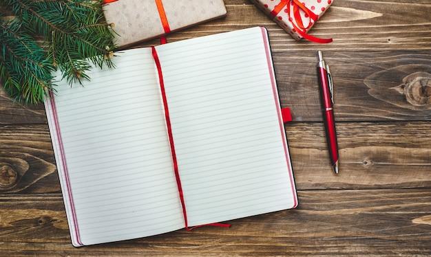 Kerstcadeaus met een decoratie op een houten bord en een notebook met een pen voor records