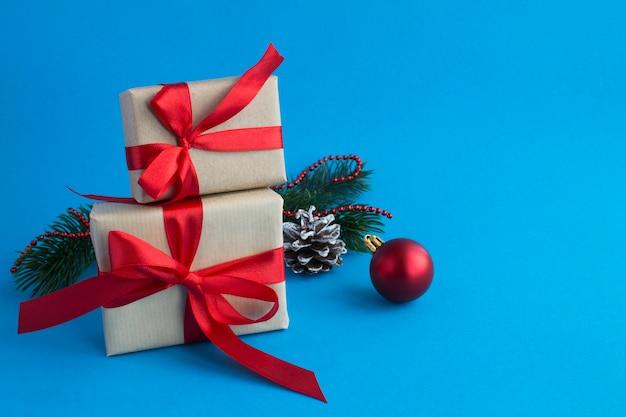 Kerstcadeaus met gebonden rode strik op de blauwe achtergrond. ruimte kopiëren. detailopname.