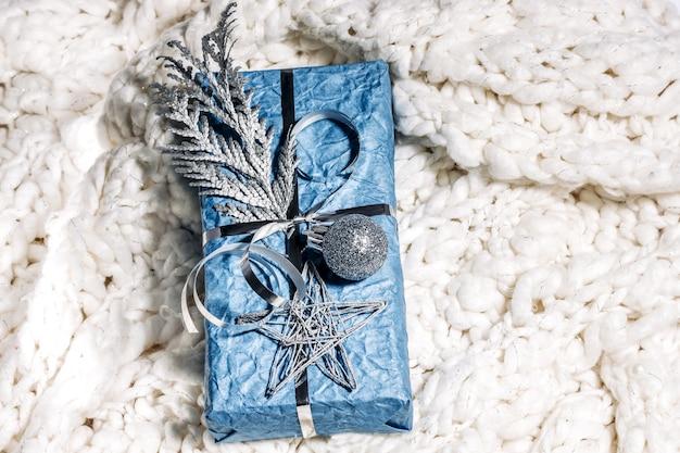 Kerstcadeaus met geschenkdoos in zilverblauwe kleur versierd met dennenappels en twijgen op witte gebreide plaid, voorbereiding op vakantie. kerstcadeaus en nieuwjaar. handgemaakt. selectieve aandacht.