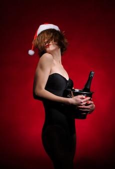 Kerstcadeaus. model meisje in kerstmuts. meisje met champagne en glazen, geïsoleerd