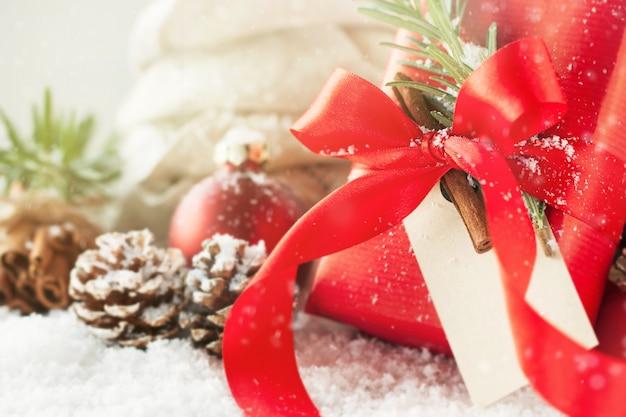 Kerstcadeaus of geschenken met elegante boog en kerstversiering op heldere besneeuwde achtergrond, kerst concept