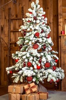 Kerstcadeaus onder de prachtige besneeuwde boom. nieuwjaar interieur
