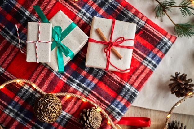 Kerstcadeaus op de achtergrond van een rode wollen geruite plaid met slingers van kegels en dennentakken