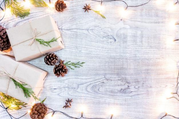 Kerstcadeaus op een witte houten achtergrond met dennen en dennenappels
