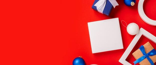 Kerstcadeaus, podium en speelgoed op een rode achtergrond. bovenaanzicht, plat gelegd. banier.
