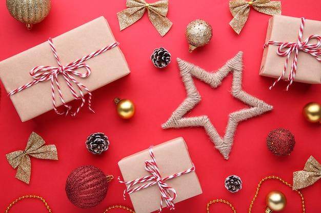 Kerstcadeaus presenteert met decoraties op een rode achtergrond.