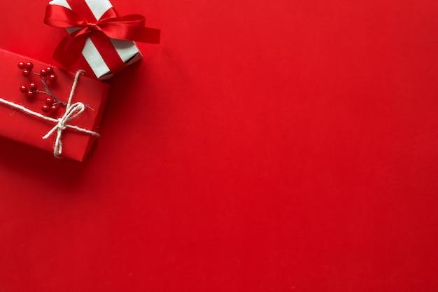 Kerstcadeaus presenteert op rode achtergrond. eenvoudige, klassieke rode en witte verpakte geschenkdozen met strikjes en feestelijke decoraties voor de feestdagen