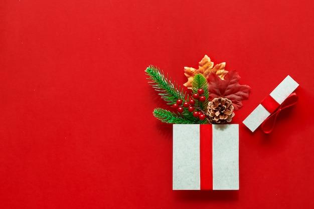Kerstcadeaus presenteert papierkunst op rode achtergrond met feestelijke vakantiedecoratie, bladeren, dennentakken, dennenappel,