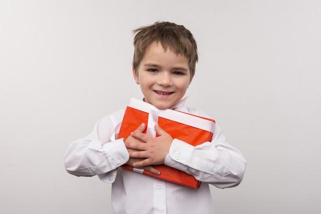 Kerstcadeaus. schattige kleine jongen knuffelen een cadeautje terwijl hij blij is met kerstmis
