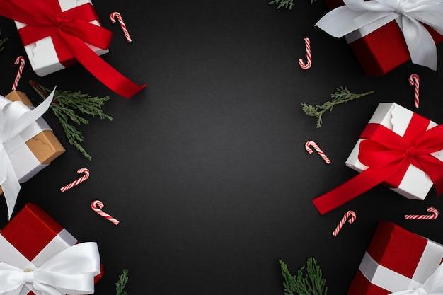 Kerstcadeaus, tak pijnboom en kerst stok op een zwarte achtergrond