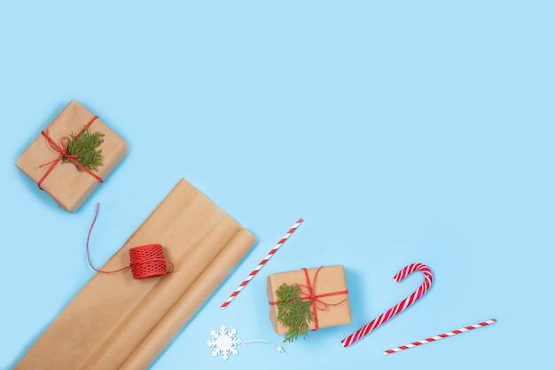 Kerstcadeaus verpakken in kraftpapier met eco-accessoires kerstboomtakken, geschenkdozen en touwen op een blauwe tafel.