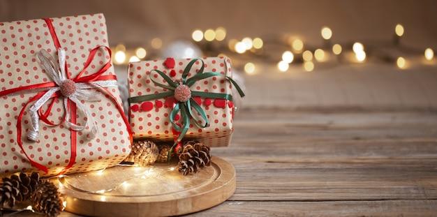 Kerstcadeaus verpakt in ambachtelijk papier met linten, slinger en decoratieve kegels op onscherpe achtergrond kopie ruimte.