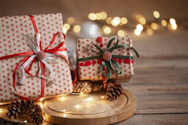 Kerstcadeaus verpakt in ambachtelijk papier met linten, slinger en decoratieve kegels op onscherpe achtergrond.
