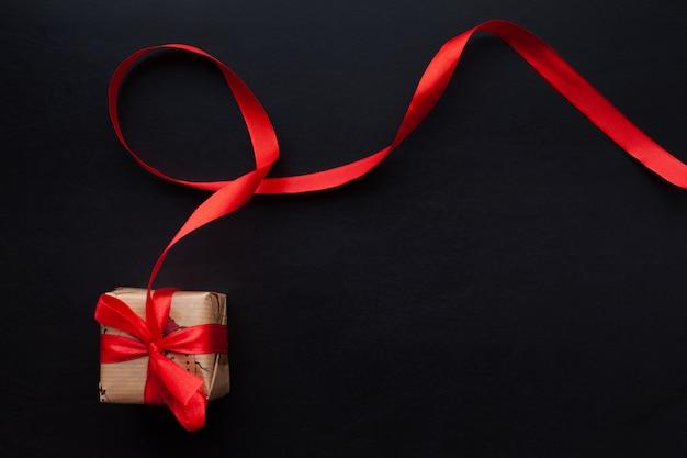 Kerstcadeaus verpakt in een rood lint op een zwarte achtergrond