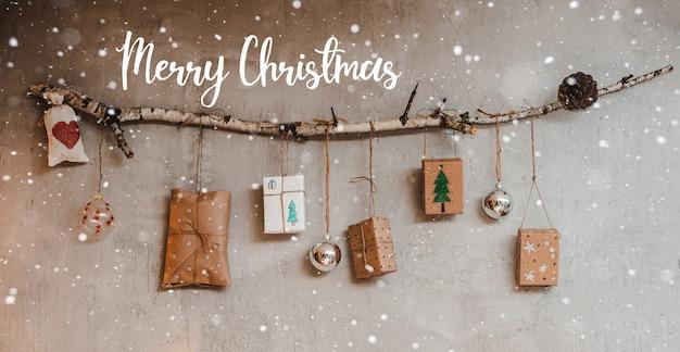 Kerstcadeaus verpakt met kraftpapier en handgemaakte decoraties hangen aan een touw dat aan een stok is vastgebonden tegen een grijze betonnen muur.