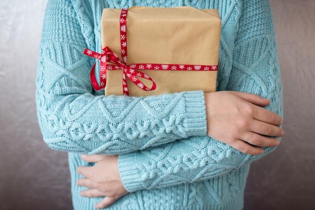 Kerstcadeaus. vrolijk kerstfeest. gebreide wanten. gebreide jurk. doos met geschenken aanwezig
