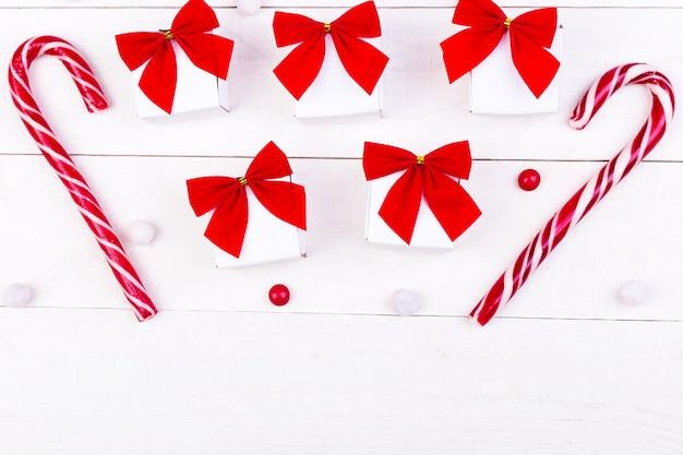 Kerstcadeaus, witte kleine dozen met rode strik en snoepjes op witte houten achtergrond