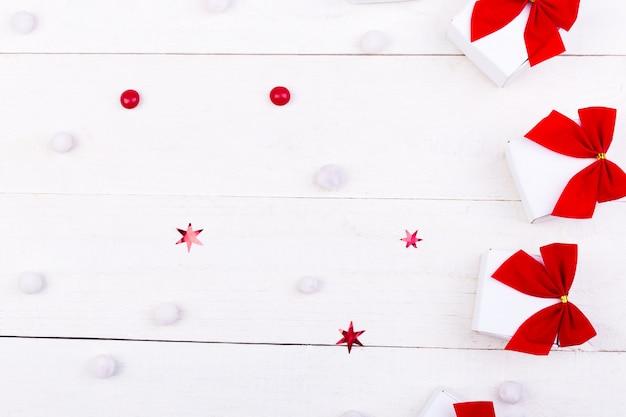 Kerstcadeaus, witte kleine dozen met rode strik en snoepjes op witte houten. plat leggen. vrolijk kerstfeest.